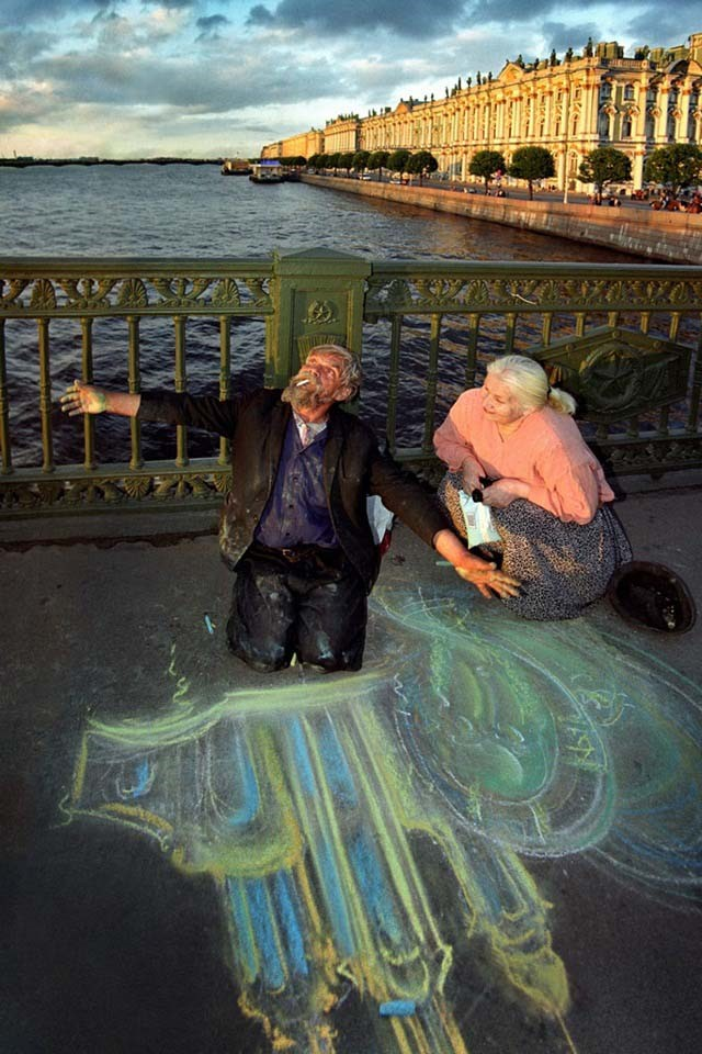 The old man draws on asphalt in the center St.Petersburg Russia